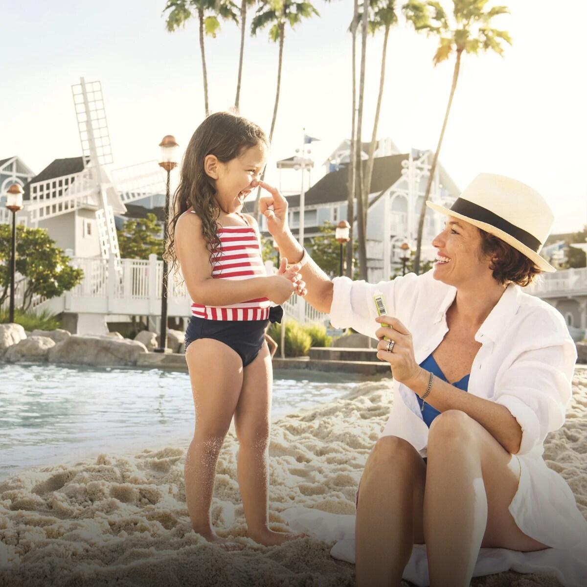 Mãe e filha a rirem-se numa praia