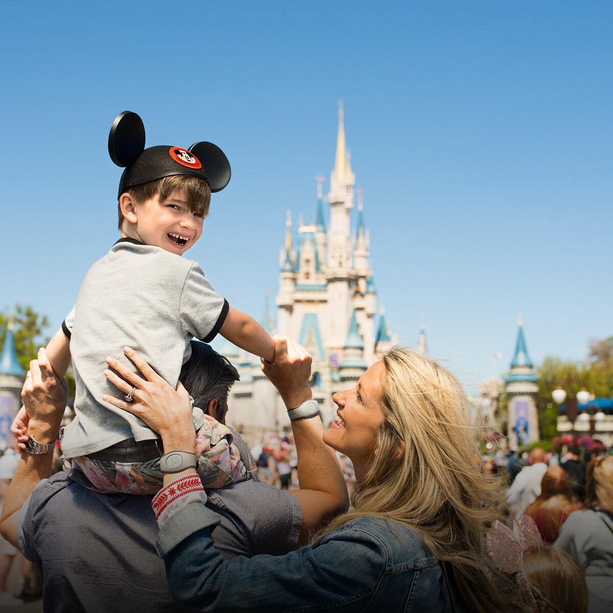 Kind met Mickey-oren wordt opgetild voor het kasteel van Assepoester in Walt Disney World