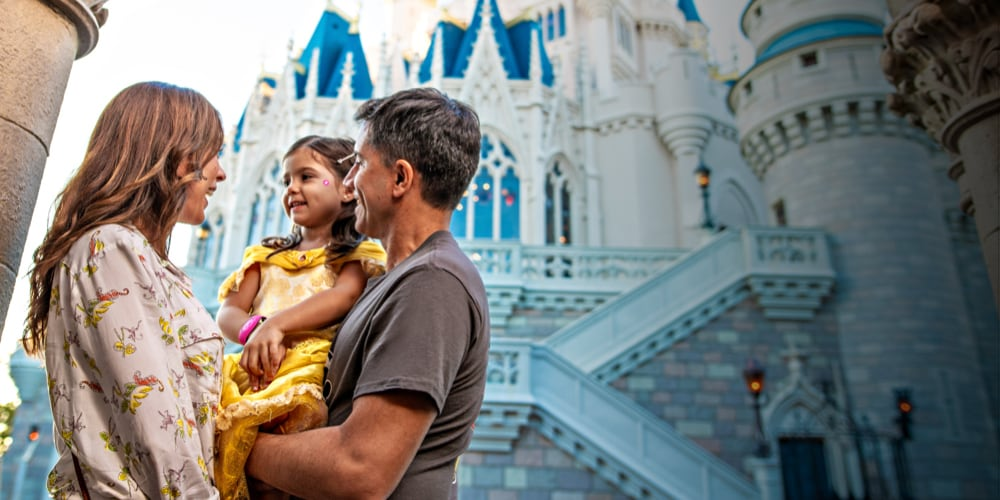 Parents holding their child in front of Cinderella's Castle at Walt Disney World