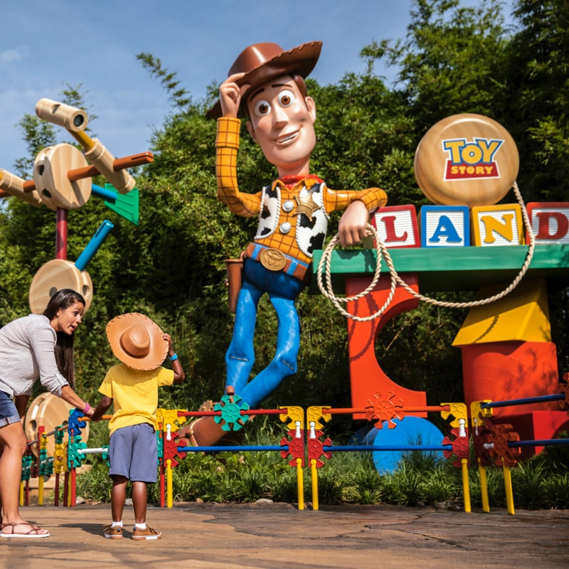A family posing for a picture outside a statue of Woody at Toy Story Land
