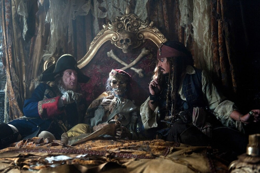 Captain Barbosa, and Captain Jack Sparrow sitting next to a skeleton