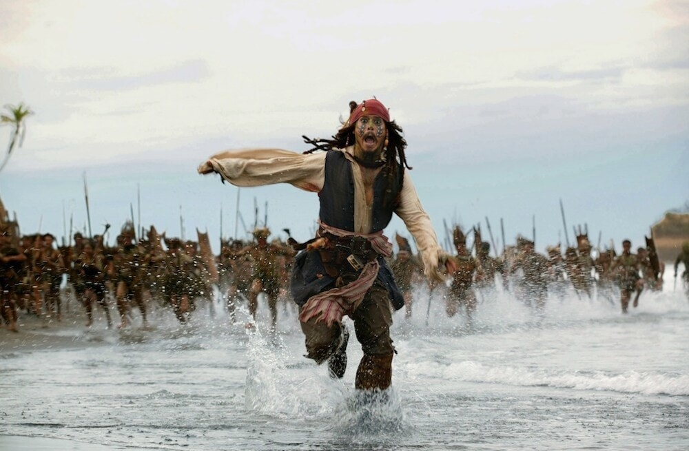 "Actor Johnny Depp as Captain Jack Sparrow running from a mob from the movie ""Pirates of the Caribbean"""