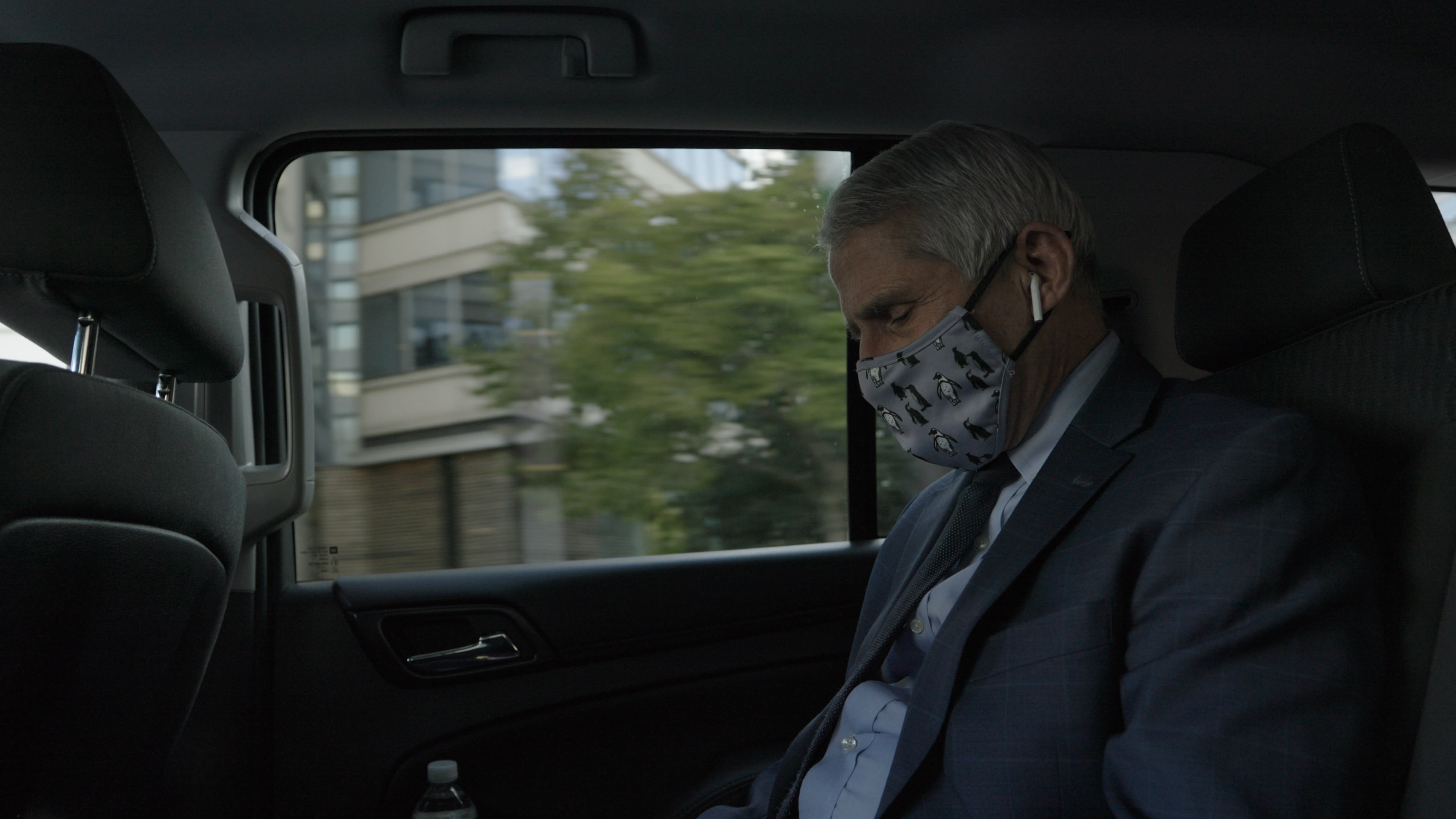 Dr. Anthony Fauci talks on the phone in his security detail car. Dr. Fauci received security after receiving death threats in 2020.  (National Geographic for Disney+)