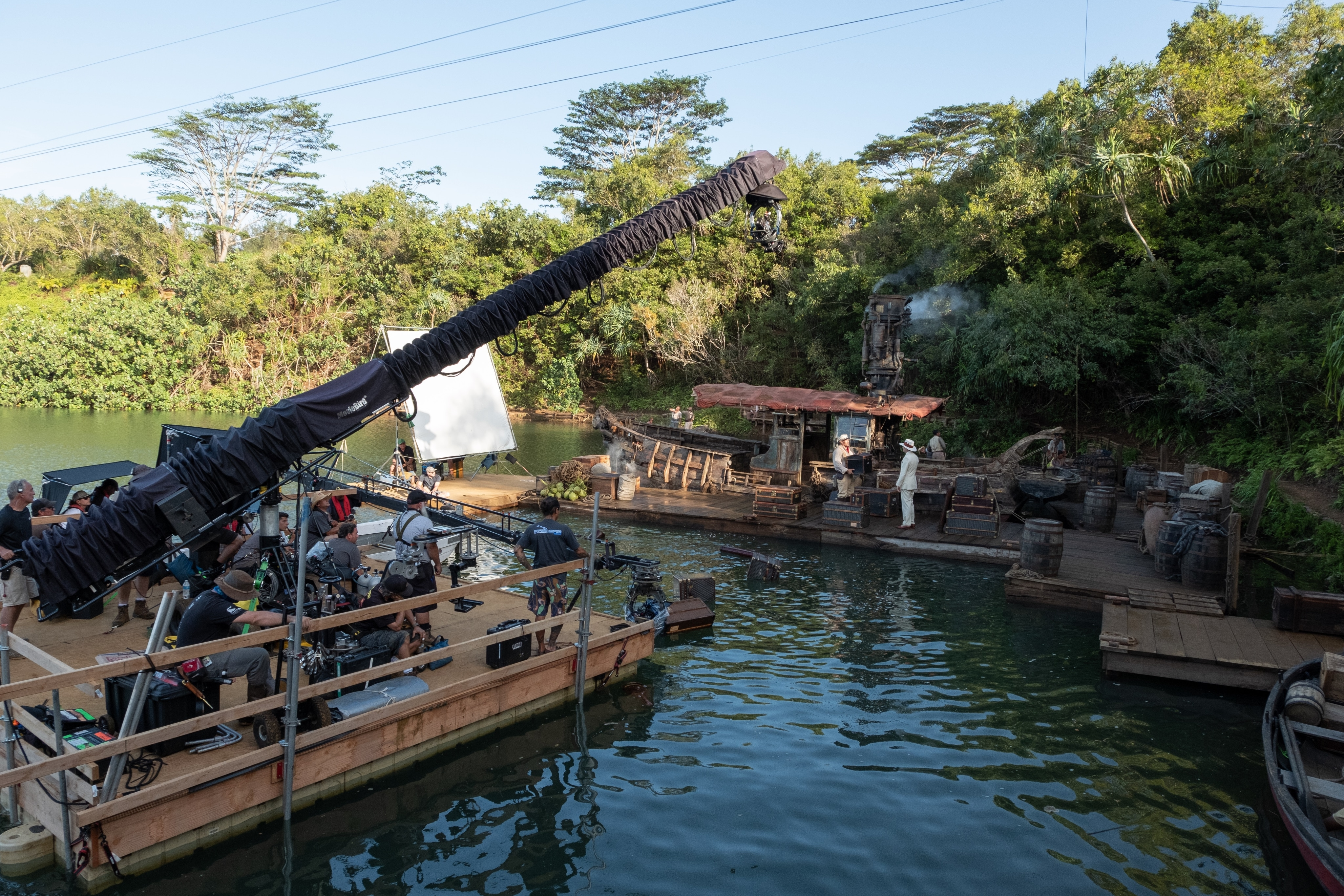Behind the scenes photo of camera crew on set filming Dwayne Johnson and Jack Whitehall at the docking area surrounded by water.