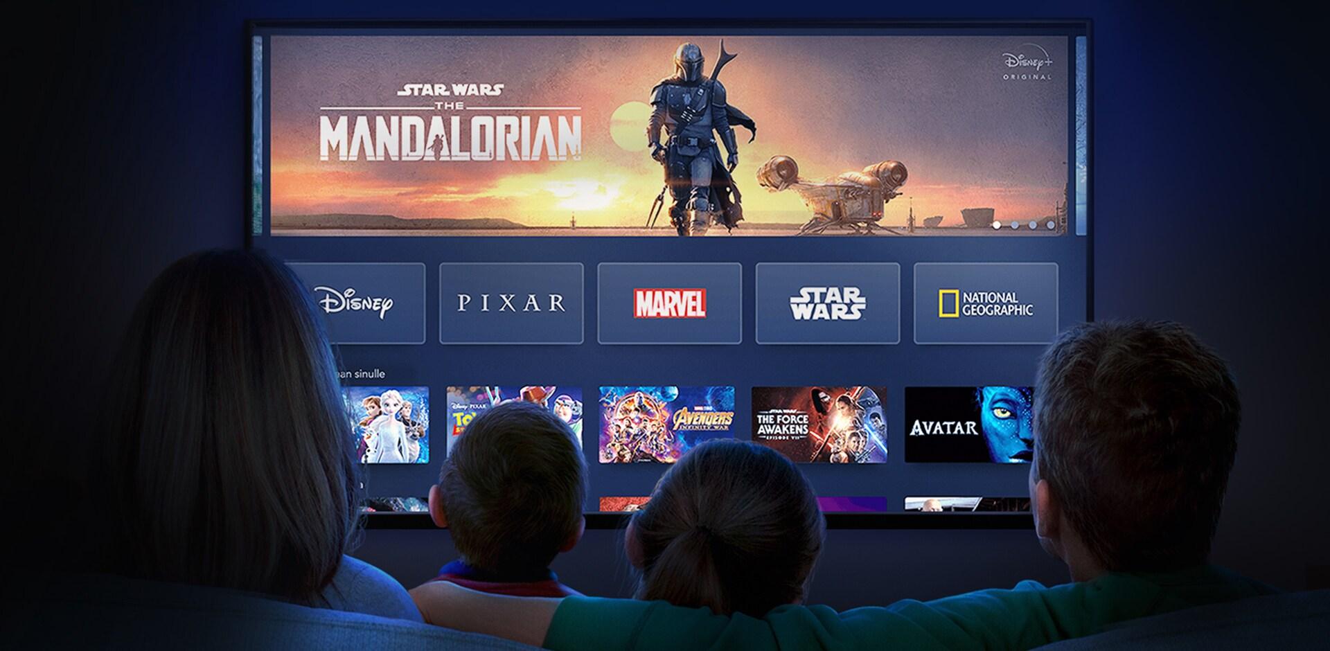Perhe istuu sohvalla katsomassa Disney+ -palvelua televisioruudulta.