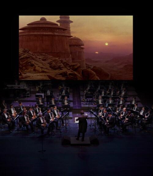 Een orkest maakt muziek en het publiek kijkt naar een fragment uit een Star Wars-film op een groot scherm op de achtergrond.