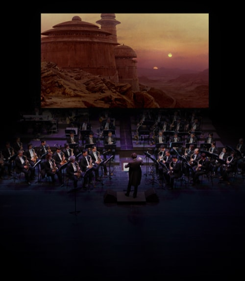 An orchestra on stage in front of a large screen showing Return of the Jedi