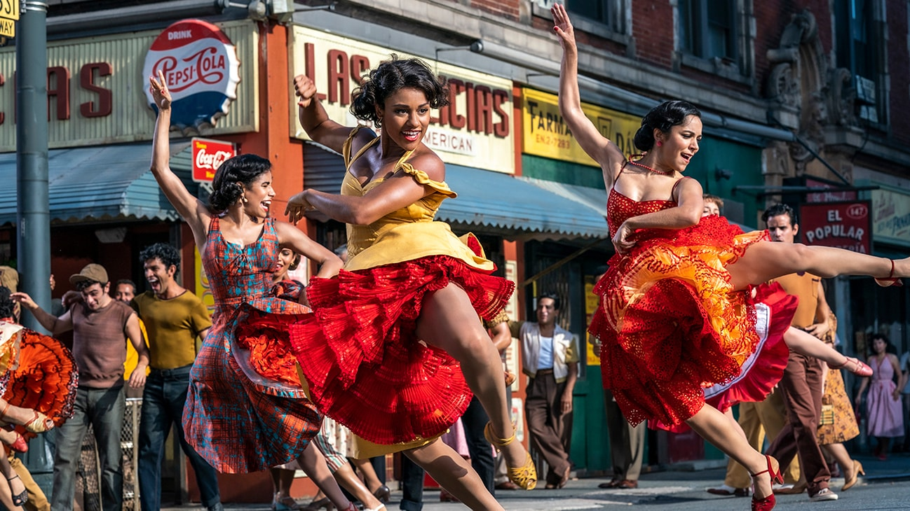 """Actor Ariana DeBose dancing with two other women from the 20th Century Studios movie """"West Side Story""""."""