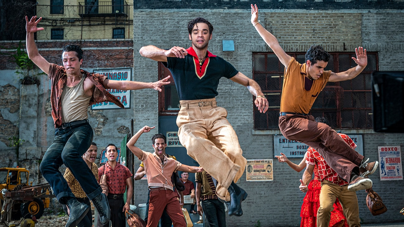 """Actor David Alvarez jumping in the air while dancing alongside two others from the 20th Century Studios movie """"West Side Story""""."""