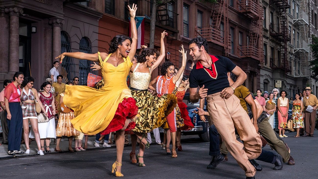 """Actors Ariana DeBose and David Alvarez dancing in a street along with several others from the 20th Century Studios movie """"West Side Story""""."""