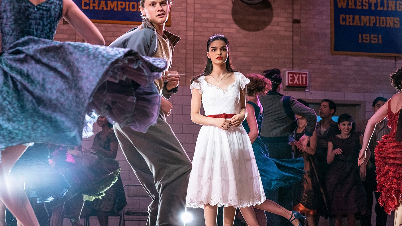 """Actor Rachel Zegler standing on a dance floor among others dancing from the 20th Century Studios movie """"West Side Story""""."""