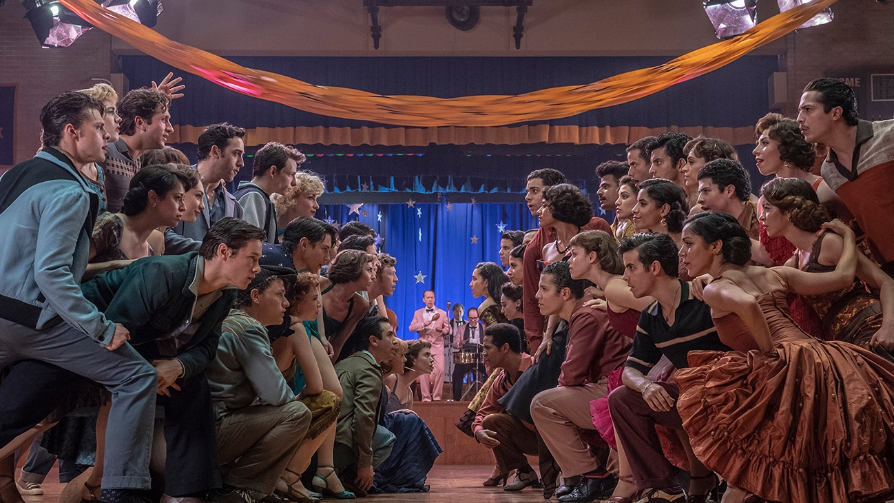 """Two groups of people staring at each other while standing and kneeling on a dance floor from the 20th Century Studios movie """"West Side Story""""."""