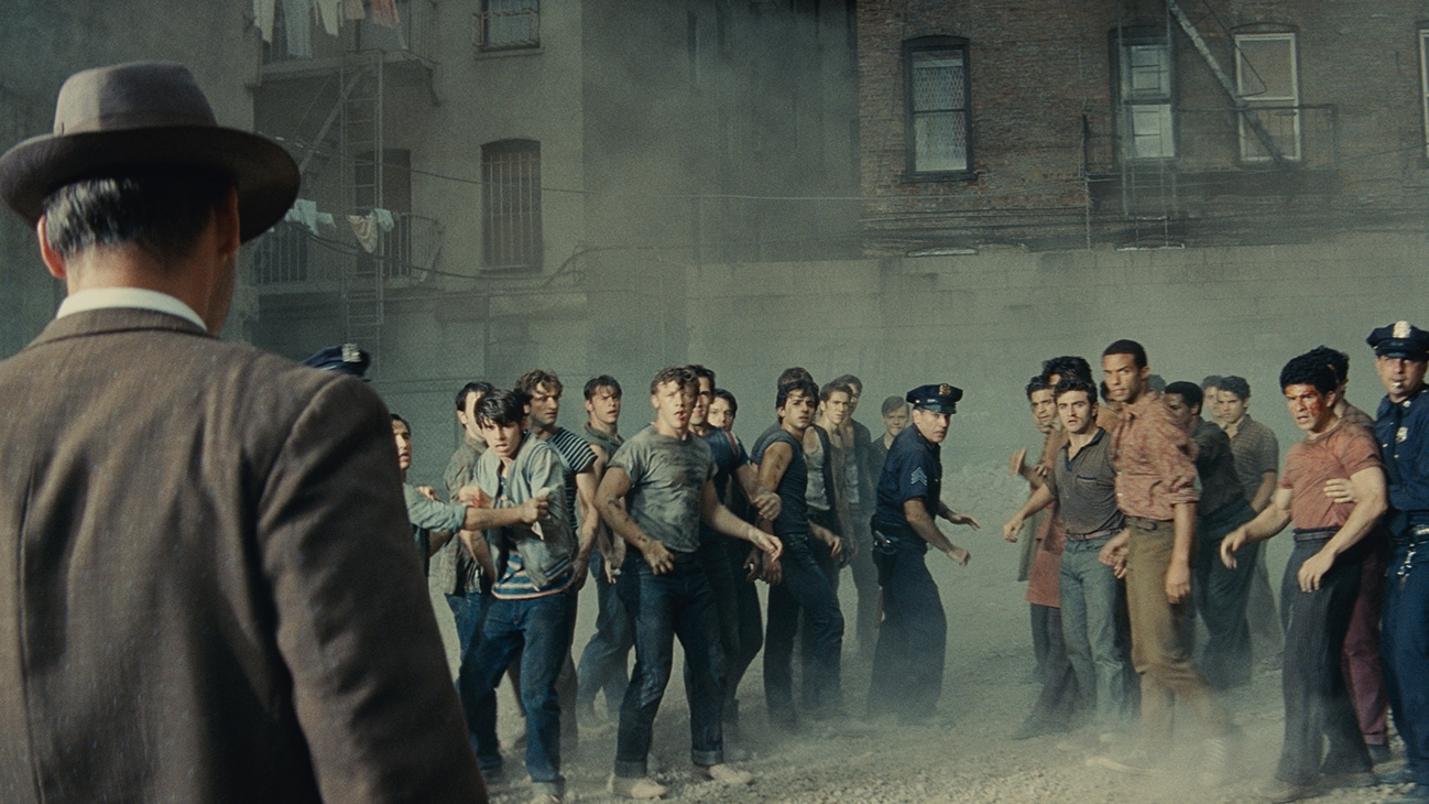 """Actors Brian d'Arcy James and Corey Stoll among a group of young men and police outside an apartment complex from the 20th Century Studios movie """"West Side Story""""."""