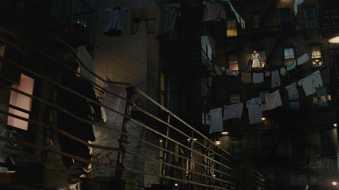 """An image of actor Ansel Elgort on an apartment walkway outside at night and actor Rachel Zegler from an apartment window above him from the 20th Century Studios movie """"West Side Story""""."""