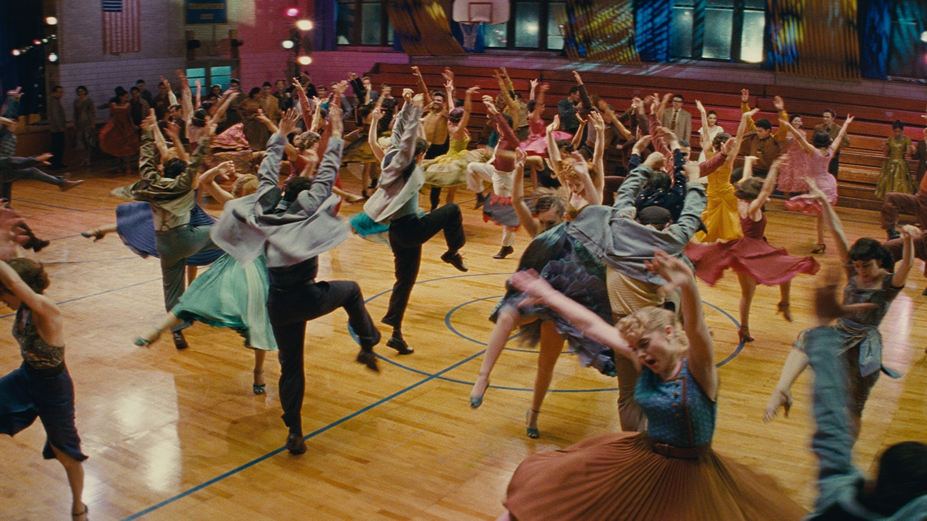 """A group of people dancing in an indoor basketball court from the 20th Century Studios movie """"West Side Story""""."""