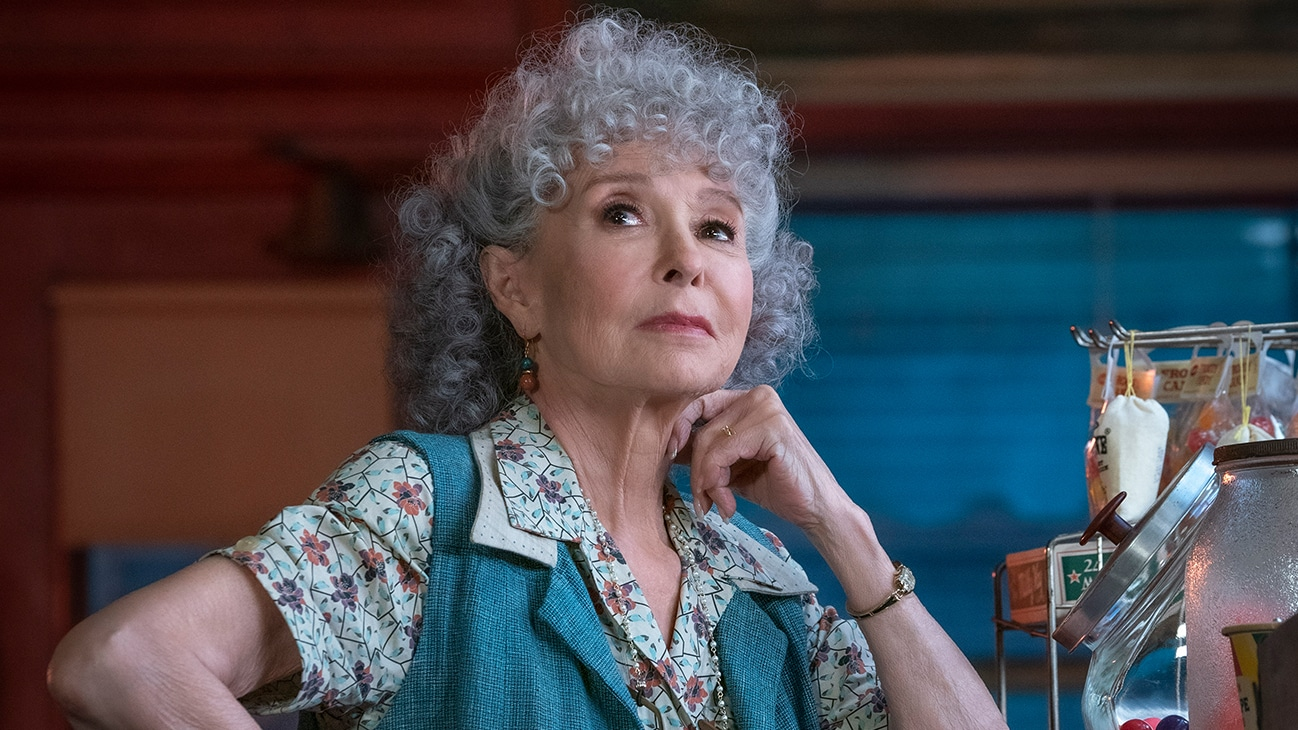 """Actor Rita Moreno sitting by a counter from the 20th Century Studios movie """"West Side Story""""."""
