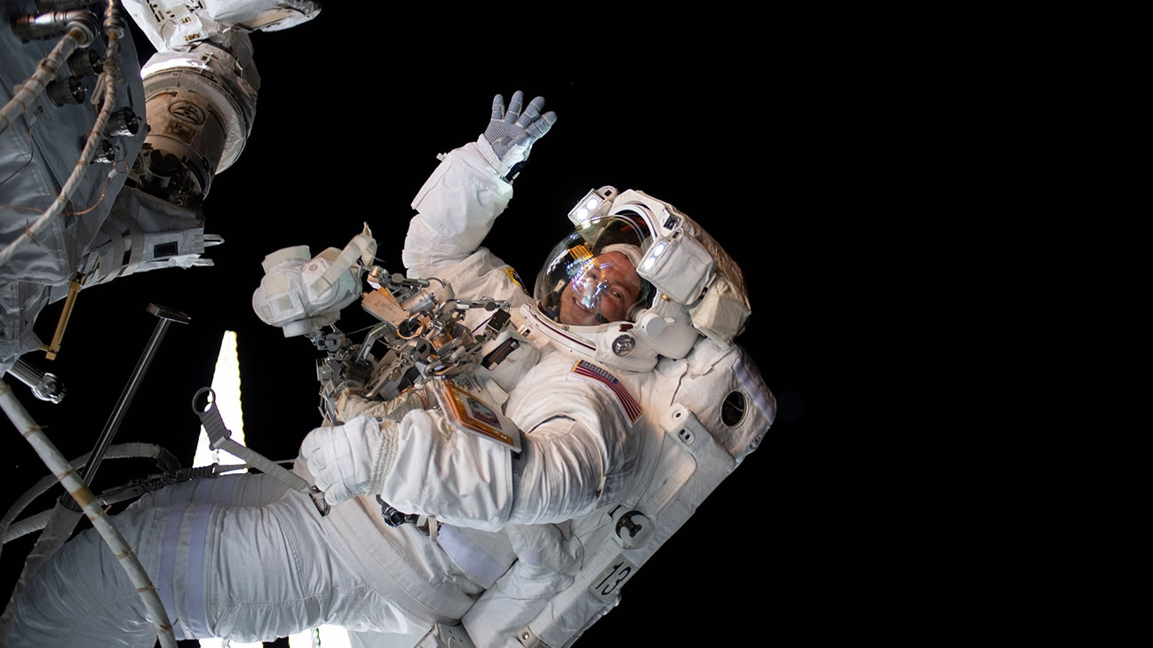 AMONG THE STARS - (Aug. 21, 2019) - NASA astronaut Andrew Morgan waves as he is photographed during a spacewalk to install the International Space Station's second commercial crew vehicle docking port, the International Docking Adapter-3 (IDA-3).  (NASA)  ANDREW MORGAN