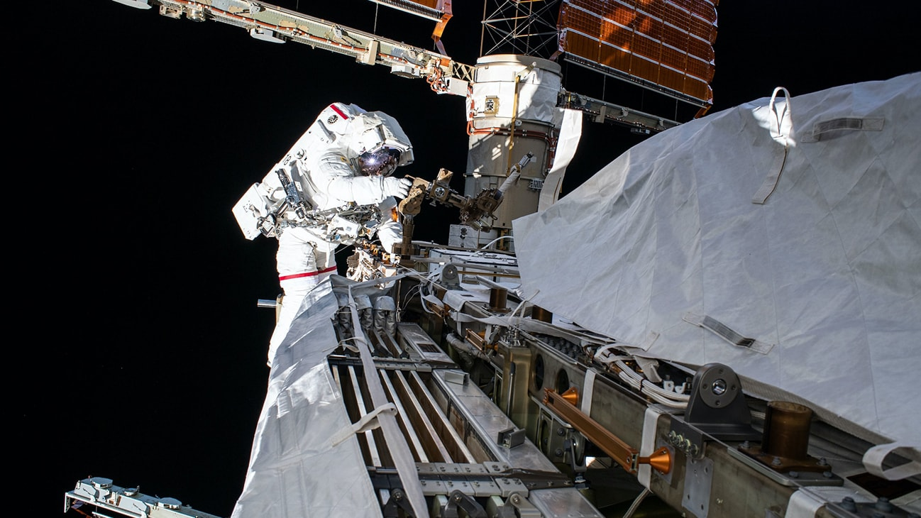 AMONG THE STARS - (Oct. 11, 2019) - NASA astronaut Andrew Morgan works while tethered on the Port 6 truss segment of the International Space Station to replace older hydrogen-nickel batteries with newer, more powerful lithium-ion batteries. The batteries store and distribute power collected from the station's basketball court-sized solar arrays directly behind Morgan. (NASA)  ANDREW MORGAN