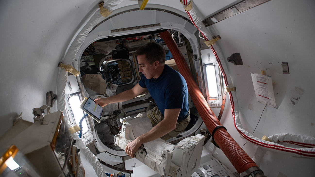 AMONG THE STARS - (June 24, 2020) - NASA astronaut and Expedition 63 Commander Chris Cassidy reviews maintenance procedures on a computer while working on U.S. spacesuit components inside the International Space Station's Quest airlock. (NASA)  CHRIS CASSIDY