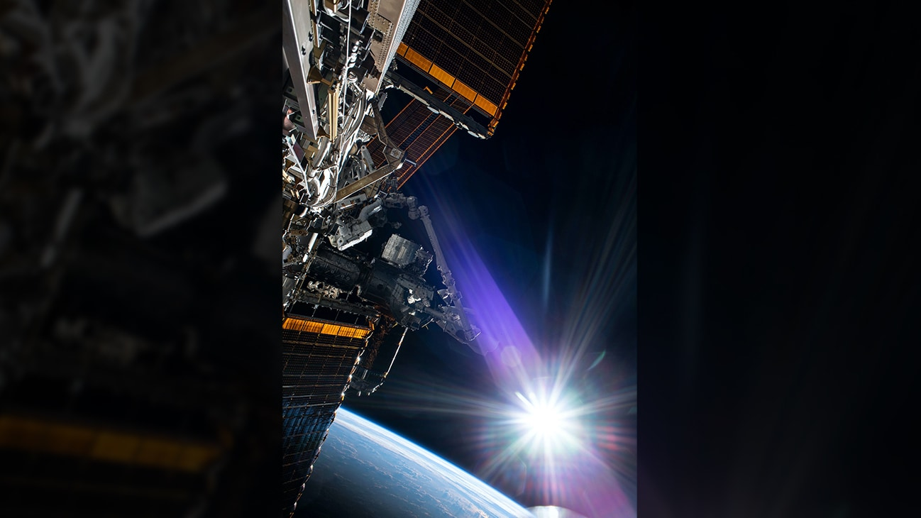 AMONG THE STARS - (July 21, 2020) - The sun beams just above the Earth's horizon as NASA astronaut and Expedition 63 Commander Chris Cassidy (center left) conducts his fourth spacewalk this year at the International Space Station. Cassidy has completed 10 spacewalks throughout his career for a total of 54 hours and 51 minutes spacewalking time. (NASA)  CHRIS CASSIDY