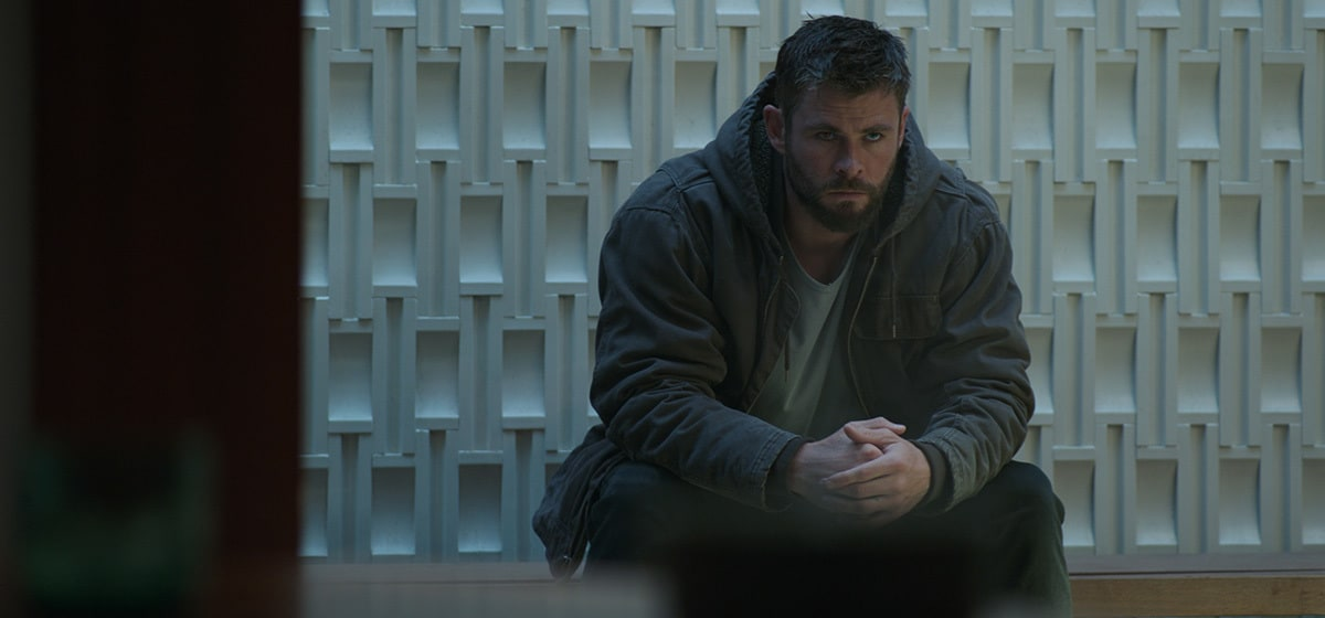 Chris Hemsworth, who plays Thor in Avengers: Endgame, sitting in front of a white textured wall