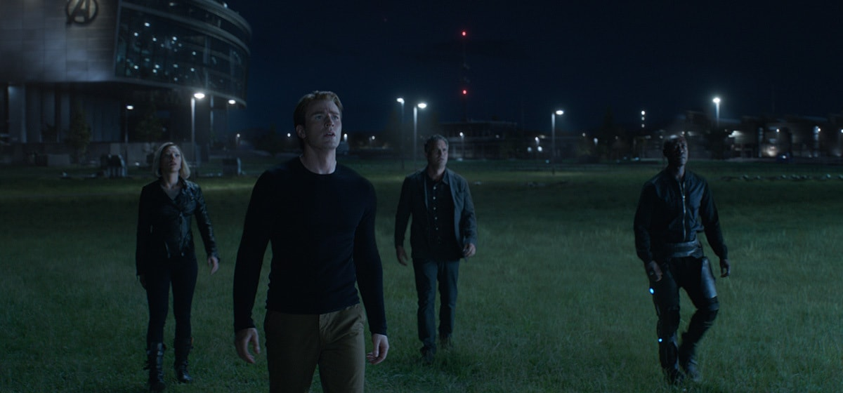 Black Widow/Natasha Romanoff (Scarlett Johansson), Captain America/Steve Rogers (Chris Evans), Bruce Banner (Mark Ruffalo), and War Machine/James Rhodes (Don Cheadle) on the grass in front of Avengers Compound and looking at the sky
