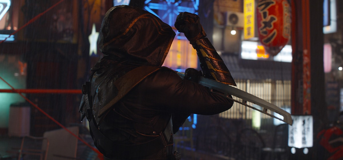Jeremy Renner, who plays Hawkeye, walking through a city at night with his hood up in Avengers: Endgame