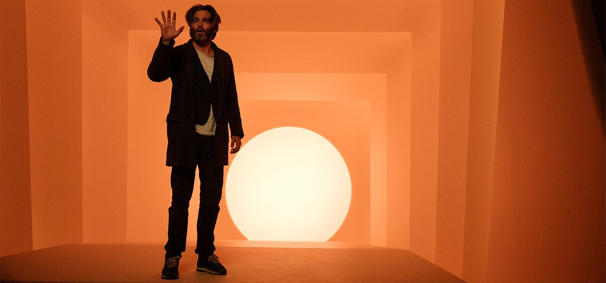 """Dr. Alex Murry (played by Chris Pine) in an orange room holding his right hand up in the movie """"A Wrinkle in Time"""""""