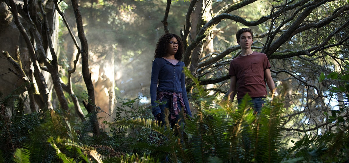 Meg Murry (played by Storm Reid) and Calvin (played by Levi Miller) in the forest in A Wrinkle in Time