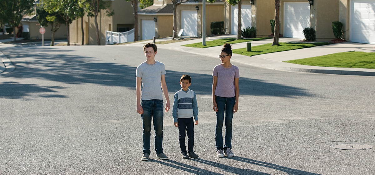 """Meg (played by Storm Reid), Charles Wallace (played by Deric McCabe), and Calvin (played by Levi Miller) standing in the middle of a residential street in the movie """"A Wrinkle in Time"""""""