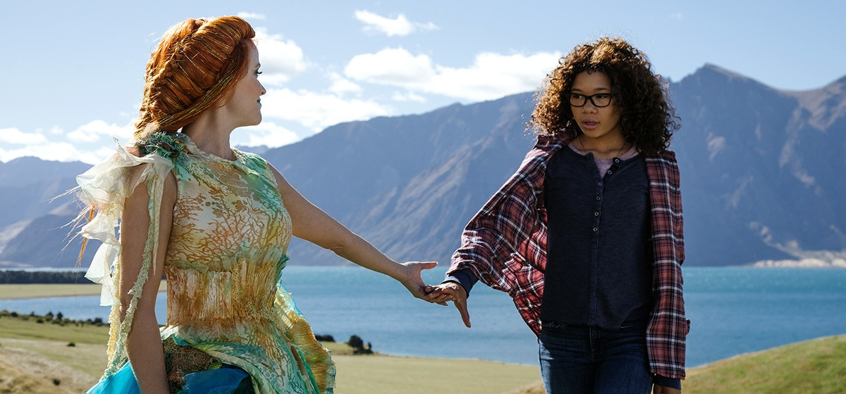 """Meg (played by Storm Reid) and Mrs Whatsit (played by Reese Witherspoon) holding hands in a field in the move """"A Wrinkle in Time"""""""