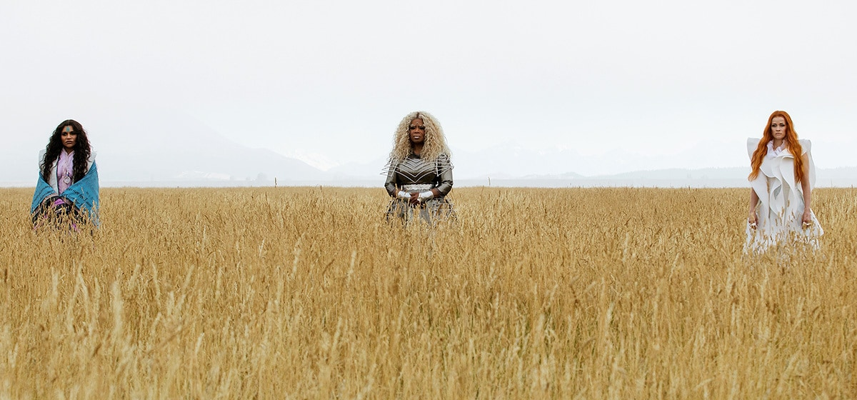"""Mrs. Who (played by Mindy Kaling), Mrs. Which (played by Oprah Winfrey) and Mrs. Whatsit (played by Reese Witherspoon) standing in a field of wheat in the movie """"A Wrinkle in Time"""""""