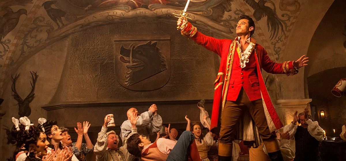 """Luke Evans (as Gaston) standing on top of a table in a bar in the movie """"Beauty and the Beast"""""""