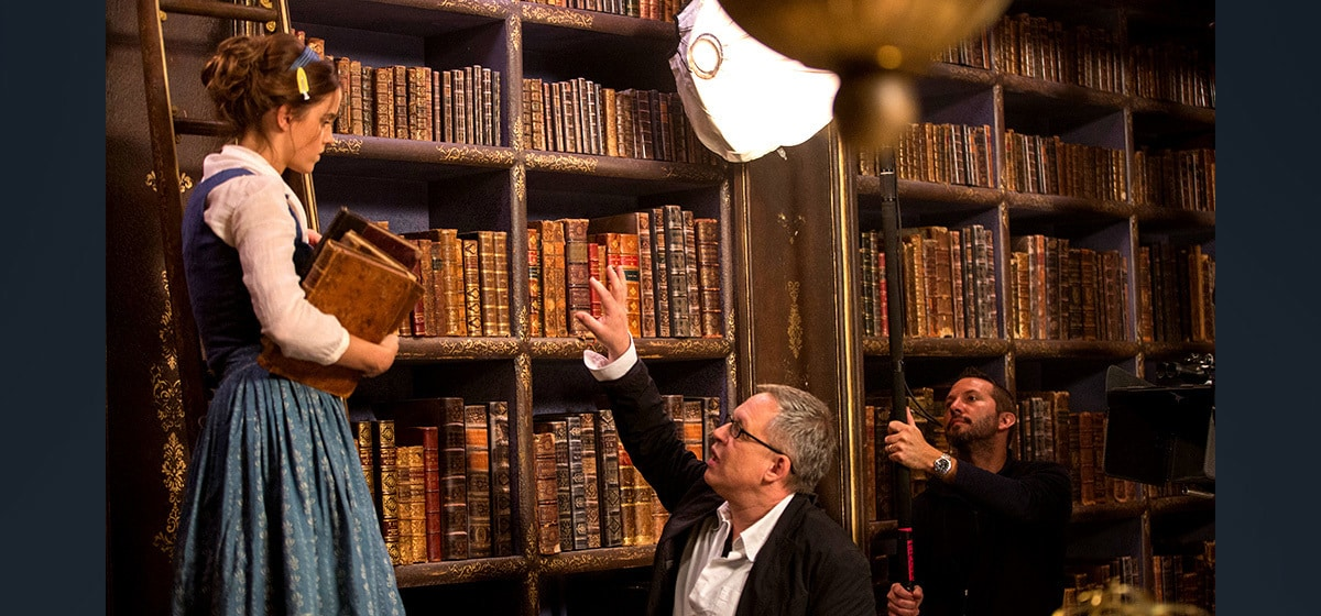 """Director Bill Condon instructs Emma Watson (Belle) as she stands on a ladder in """"Beauty and the Beast"""""""