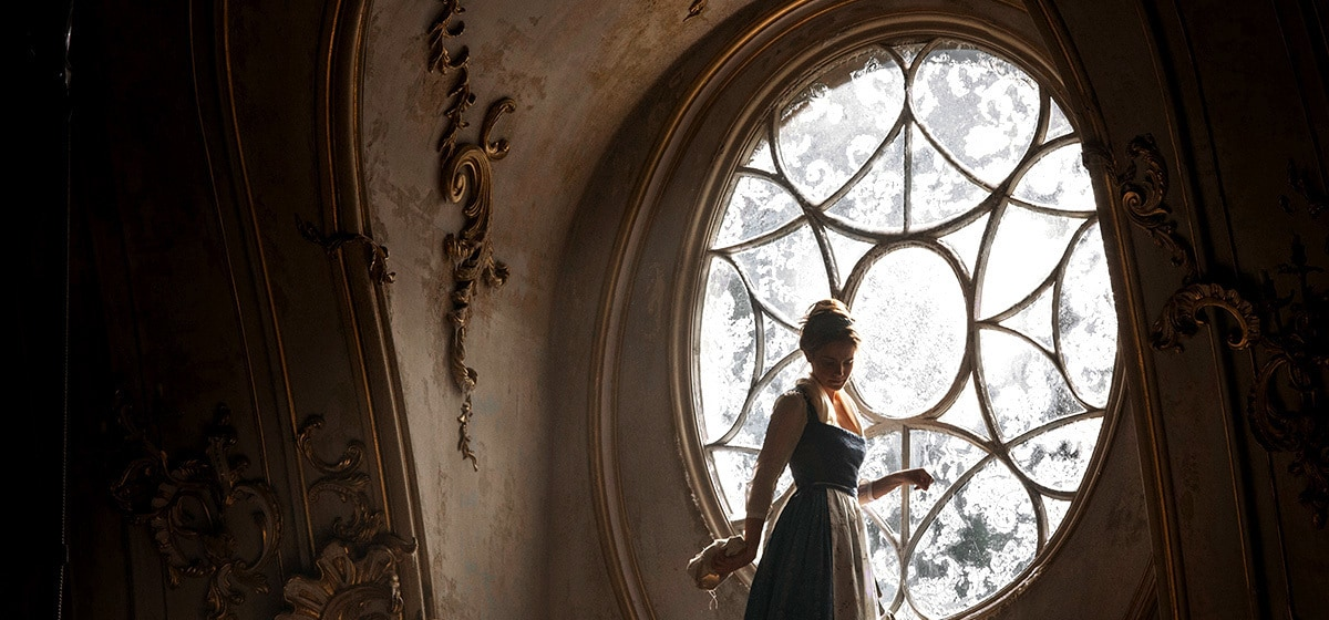 """Emma Watson (Belle) cleans a large window in the castle in """"Beauty and the Beast"""""""