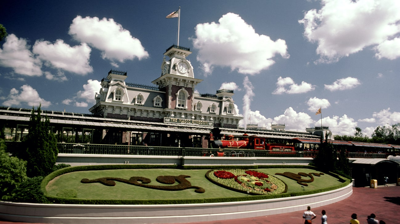 Image of a the Disney train locomotive and passenger cars at the station.