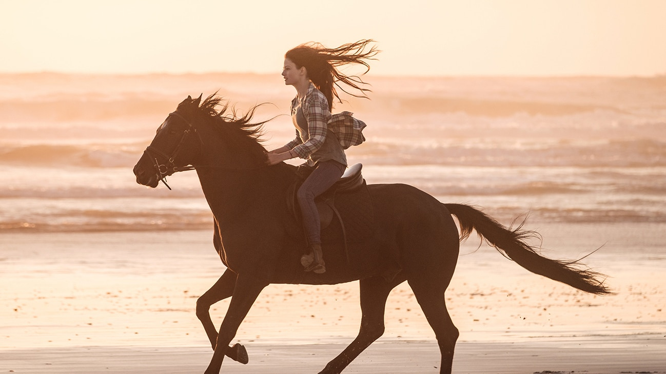 Girl riding a horse on the beach from the movie Black Beauty.