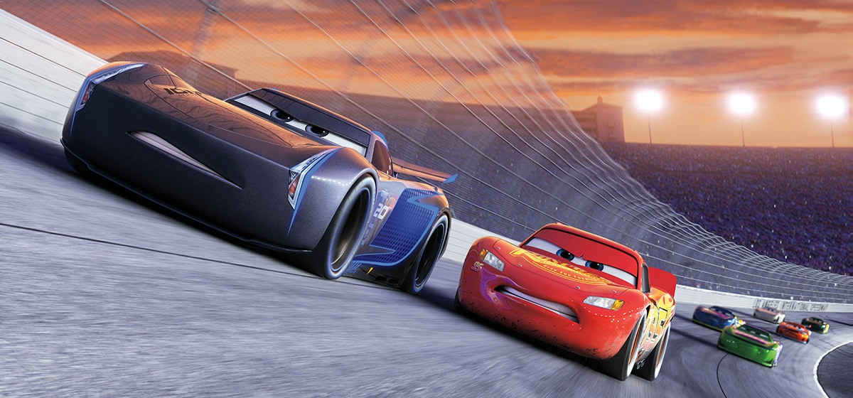 Owen Wilson as Lightning McQueen and Armie Hammer as Jackson Storm on the race track followed by a number of other race cars in Cars 3