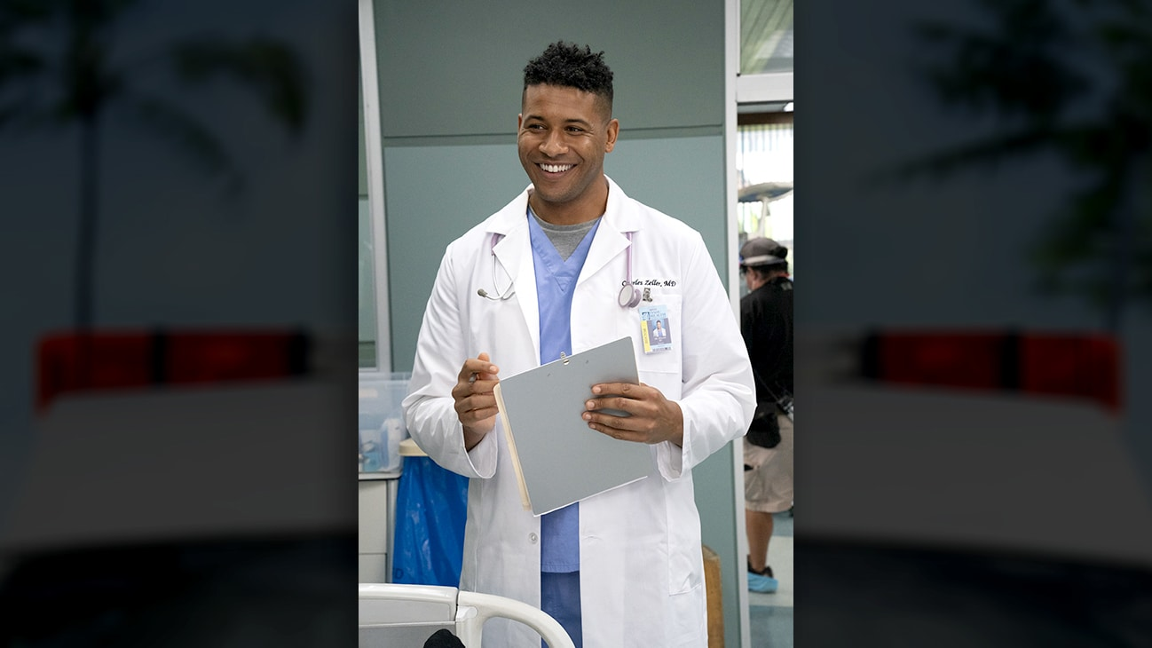 Dr. smiling and standing holding a clipboard. From the Disney+ Original series Doogie Kamealoha, M.D.