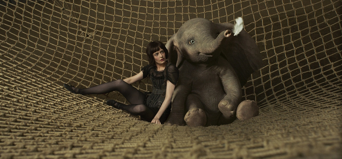 """Eva Green (Colette Marchant) and Dumbo lay in a net from the movie """"Dumbo"""""""