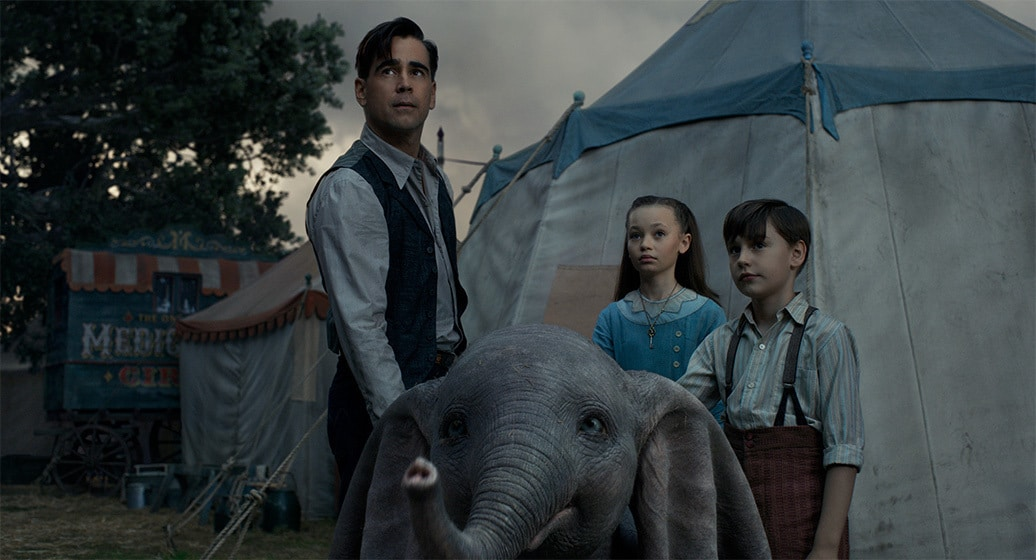 """Colin Farrell (Holt Farrier), Nico Parker (Milly Farrier) and Finley Hobbins (Joe Farrier) stand behind Dumbo from the movie """"Dumbo"""""""