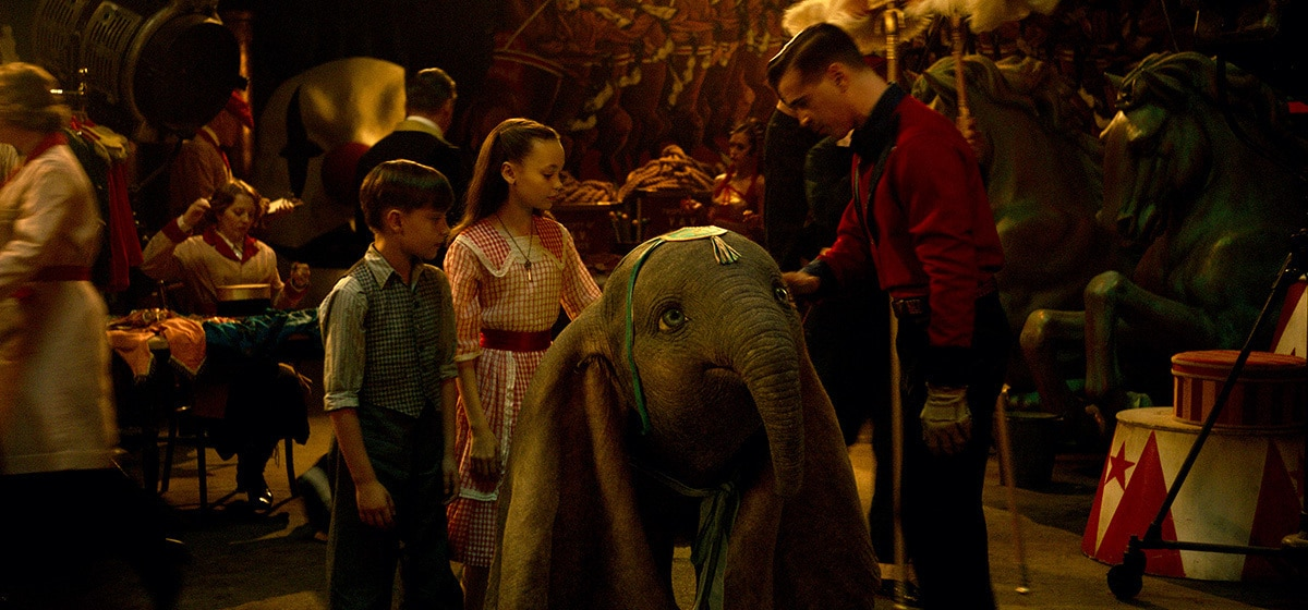 """Colin Farrell (Holt Farrier), Nico Parker (Milly Farrier) and Finley Hobbins (Joe Farrier) stands with Dumbo from the movie """"Dumbo"""""""