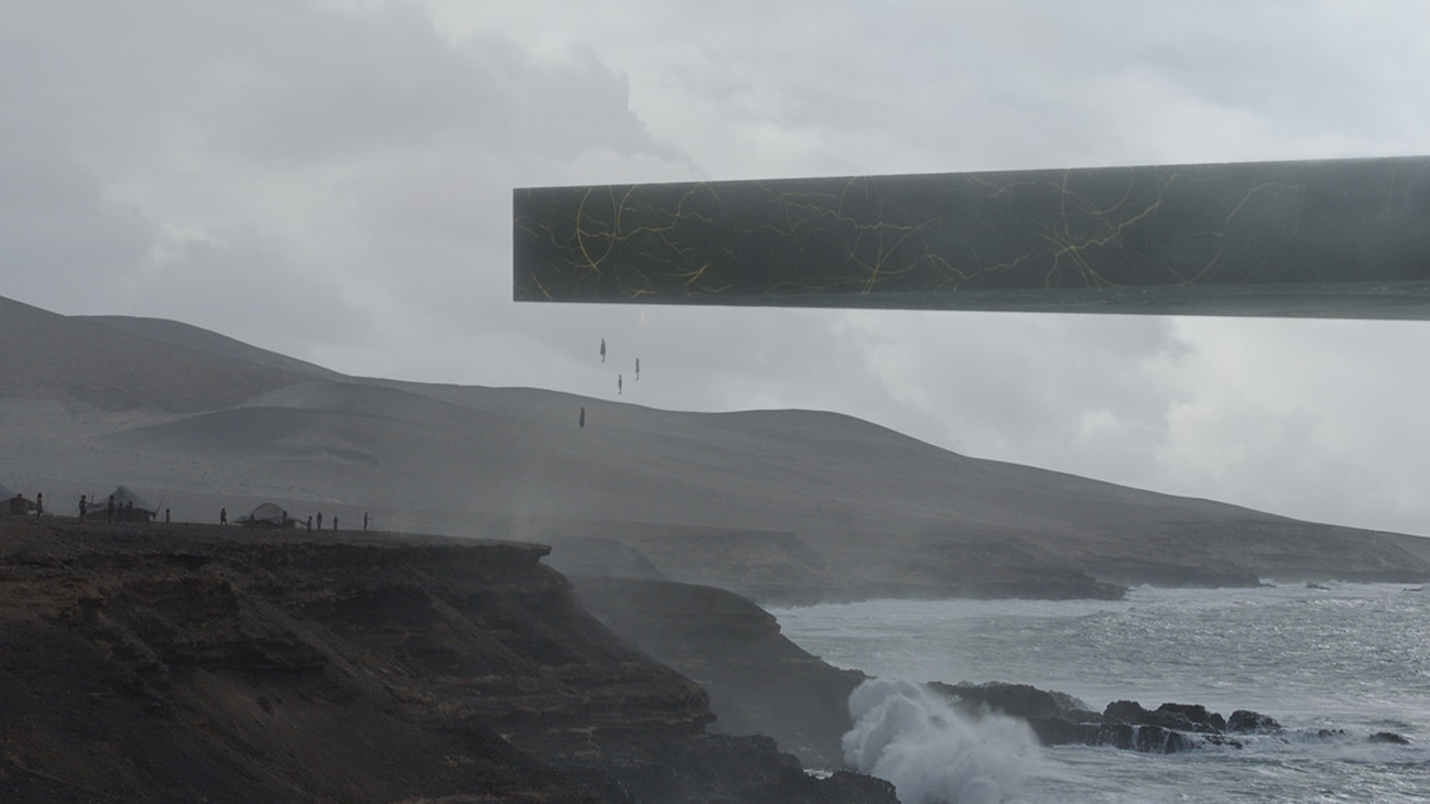 Image of a large and flat object hovering above the ocean by cliffs with several human-like objects just below it from the Marvel Studios movie Eternals.