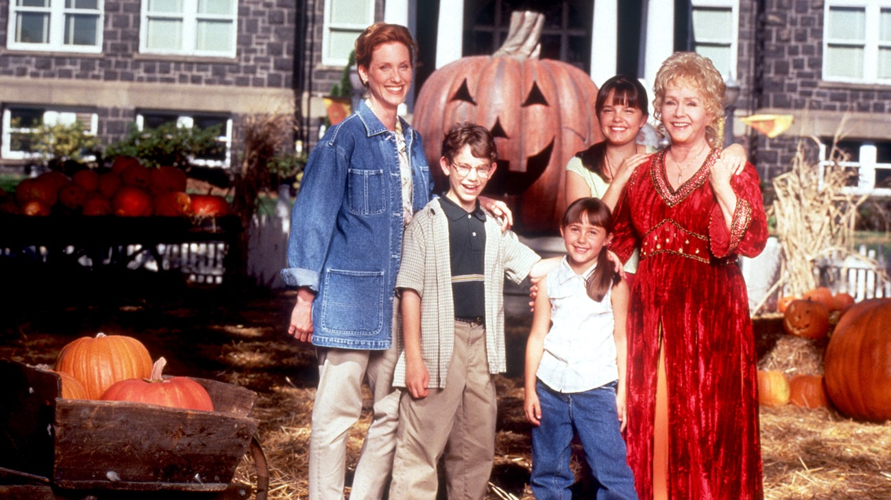 """Debbie Reynolds, Kimberly J. Brown, Judith Hoag, Emily Roeske, and Joey Zimmerman from the Disney movie """"Halloweentown"""" standing in a pumpkin patch in front of City Hall."""