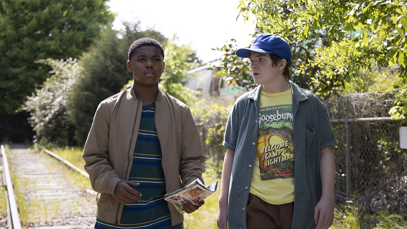 """Cedric Joe and Jack Gore talking to each other by train tracks from the Just Beyond episode """"The Treehouse"""". (Disney/Fernando Decillis)"""