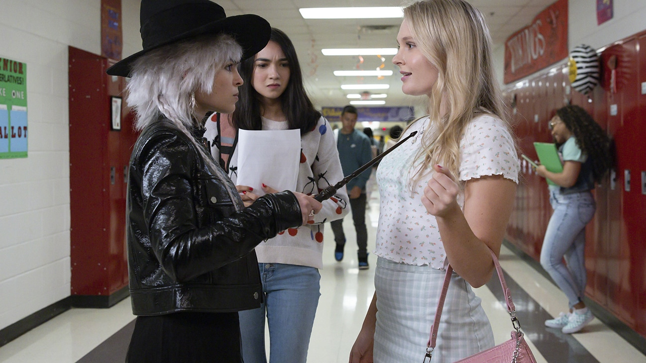 """Actors Prishkulnik, Rachel Marsh, and Sarah Borne talking in the middle of a school hallway from the Just Beyond episode """"Which Witch?"""" (Disney/Fernando Decillis)"""