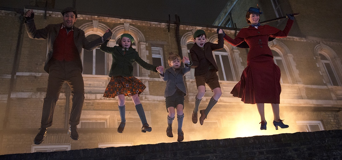 """Jack, Mary Poppins and the Banks children jumping off a wall in """"Mary Poppins Returns"""""""