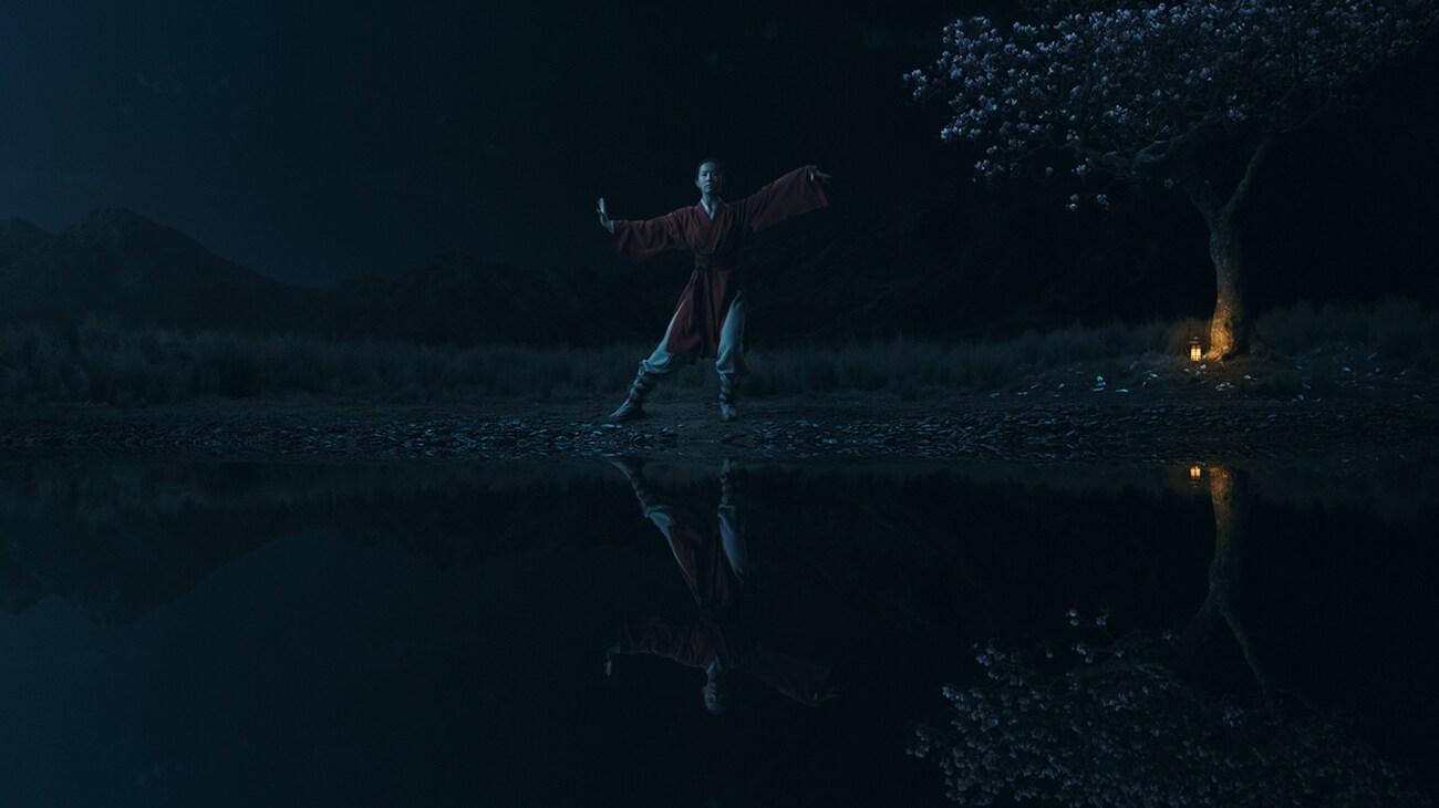 """Yifei Liu (Mulan) at a pond practicing martial arts in """"Mulan"""""""