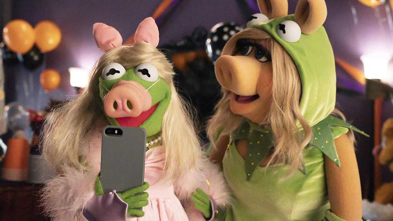 Image of Kermit the Frog and Miss Piggy dressed up as each other and taking a selfie from the Disney movie Muppets Haunted Mansion. (Disney/Mitch Haaseth)