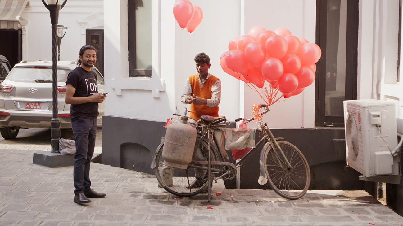 Bhaktapur, Nepal - Santosh Pandey, Co-Founder of Offering Happiness, waits for balloons to be inflated in Bhaktapur, Nepal. (Credit: Future of Work Film Inc)